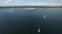 Backwards flight over water away from marina passing sailboats in Melbourne Stock Footage