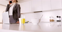 Woman talking on mobile phone in kitchen Stock Footage