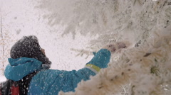 Cheerful Woman Shakes Off the Snow From the Branches Slow-Motion Stock Footage