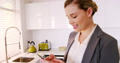 Woman using mobile phone in kitchen Stock Footage
