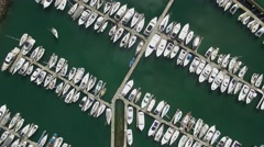Aerial shot looking straight down on moored boats in marina and spinning Stock Footage