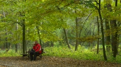 Tourist is Talking on Mobile Phone in Park Autumn Finishes the Call and Stock Footage