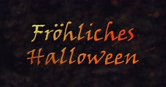 Frohliches Halloween text in German dissolving into dust to bottom Stock Footage