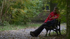 Man in Eyeglasses Having Rest on a Bench in Park Takes Glasses Off Rubs His Stock Footage