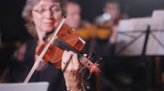 4K Symphony orchestra during a performance with focus on violinist Stock Footage