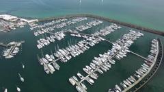 Passing above Sandringham marina flying towards sailboats revealing horizon Stock Footage