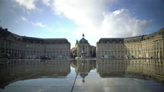 Tourists walking near mirror fountain at Place de la Bourse in Bordeaux, France Stock Footage