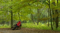 Man is Resting on Bench Crossed His Legs Looking at the Trees in Forest Park Stock Footage