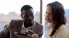 Two mixed collegues working with tablet. They discussing business ideas sitting Stock Footage