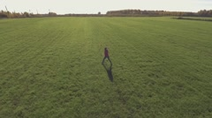 Guy and girl run towards each other on the green field Stock Footage