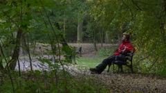 Man Has a Rest Sitting on a Bench in Cloudy Day Tourist Sits With His Legs Stock Footage