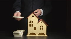 Businessman counts a money and throws it on a table near a house model Stock Footage