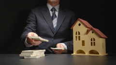 Businessman counts a money and near a house model on a table Stock Footage