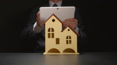 Businessman holds a tablet PC at the hands behind a house model on a table Stock Footage