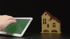 Businessman holds a tablet PC at the hands near a house model (green screen) Stock Footage