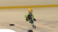 Little hockey player does an exercise on an ice Stock Footage