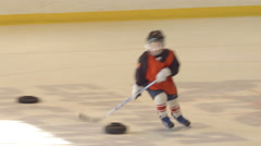 Little hockey player does an exercise on an ice (red) Stock Footage