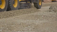 Grader machine leveling rubble stones on new road construction Stock Footage