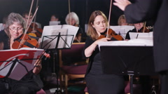 4K Orchestra during a performance, violinists following cues from the conductor Stock Footage