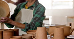Female potter examining a earthenware pot Stock Footage