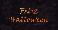Feliz Halloween text in Spanish dissolving into dust to bottom Stock Footage