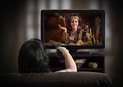 Woman watching mystical TV channel Kuvituskuvat