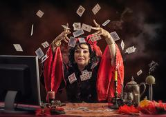 Gypsy fortune-teller tossing up playing cards Stock Photos