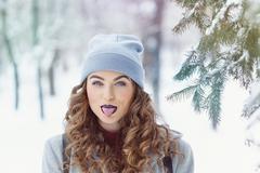 Hipster Girl winter. Show tongue. Stock Photos