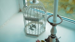 Candlestick and Bird Cage Stands on Windowsill Stock Footage
