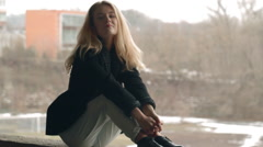 Beautiful blonde young girl fashion look smiling and sitting on parapet Stock Footage