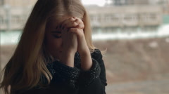 Beautiful blonde young girl fashion look smiling and sitting on parapet close-up Stock Footage