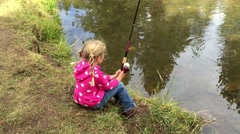Little girl fishes from the bank of a small creek HD  Stock Footage