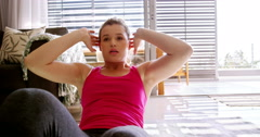 Woman doing exercise in living room Stock Footage