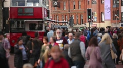 Anonymous crowds in England with a red double decker bus Stock Footage