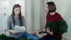 Two quarreling girls preparing Christmas tree for decorations Stock Footage