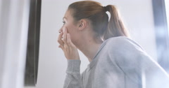 Young adult female looking in mirror examining skin Stock Footage