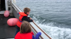 Gimbal shot of a family riding on a boat in the ocean Stock Footage