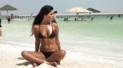 Beautiful girl sitting on the beach Stock Footage
