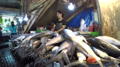 Asian woman chopping and cleaning fish at wet market stall Stock Footage