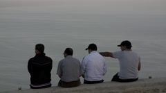 Men sitting on wall overlooking  the Sea Stock Footage