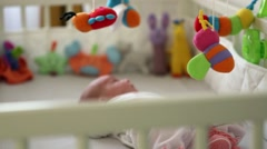 Infant baby playing with stuffed toys rotating over bed Stock Footage