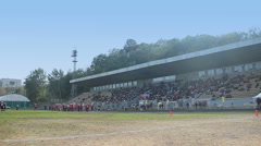 View on old football stadium, fans sitting on tribunes and waiting for the game Stock Footage