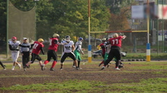 Exciting football game, cornerback attacking player with a ball, teams running Stock Footage