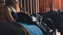 Woman Saddles up His Horse in the Stable Stock Footage