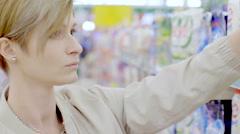 Woman choosing cleanser in supermarket Stock Footage
