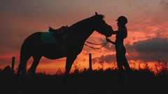 Silhouette of a Woman and Her Horse at Sunset Stock Footage
