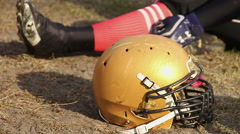 Professional football player sitting on pitch during time-out, helmet closeup Stock Footage