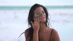 Beautiful woman rubs mud from the Dead Sea on her  face  Stock Footage