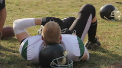 Lazy football player lying on field and relaxing, time-out during difficult game Stock Footage