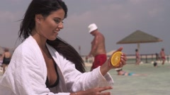 Beautiful woman squeezes orange on the beach. Stock Footage